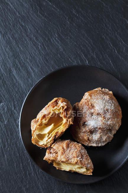 Choux тесто crullers на черной тарелке — стоковое фото