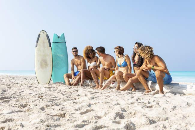 Молодые серферы отдыхают, сидя на пляже — стоковое фото