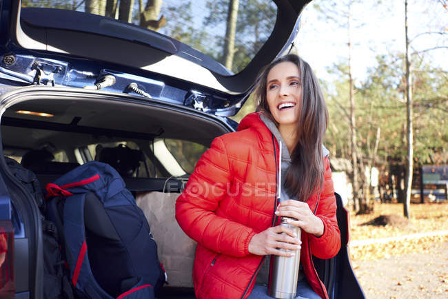 Happy woman sitting in car trunk during road trip with thermos flask — Stock Photo