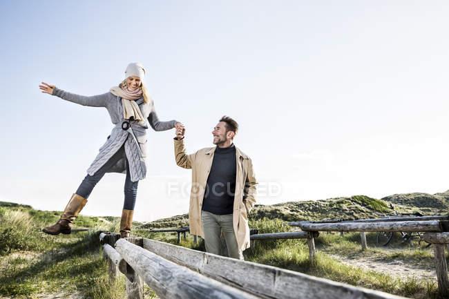 Людина допомагаючи жінці балансування на дерев'яні ставки в дюнах — стокове фото