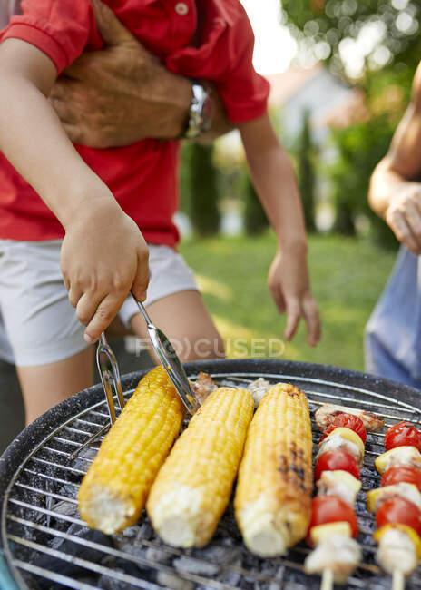 Menino transformando uma espiga de milho durante um churrasco no jardim — Fotografia de Stock
