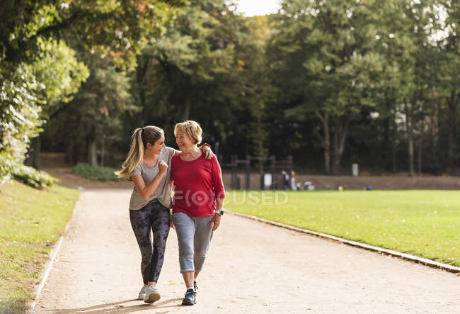 Внучка и бабушка веселятся, бегают вместе в парке — стоковое фото
