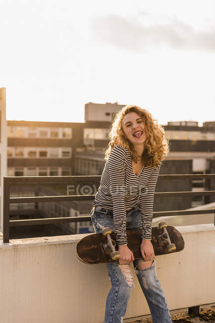 Portrait of cheeky young woman with skateboard on roof terrace at sunset — Stock Photo