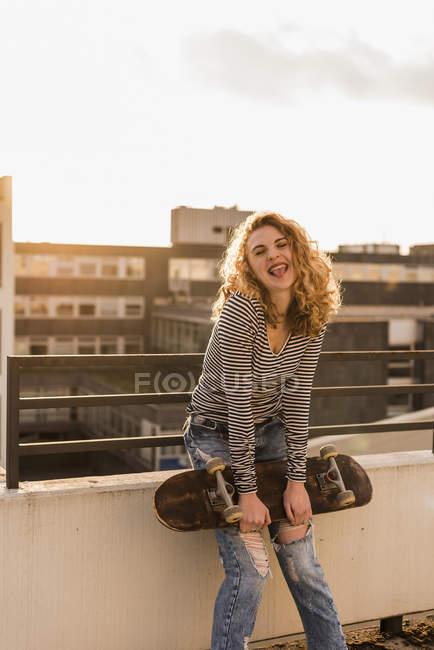 Porträt einer frechen jungen Frau mit Skateboard auf der Dachterrasse bei Sonnenuntergang — Stockfoto