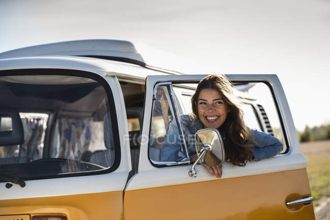 Pretty woman on a road trip with her camper, looking out of car window — Stock Photo