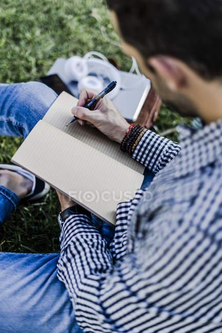 Людина, яка сидить на луці, робить нотатки. — стокове фото