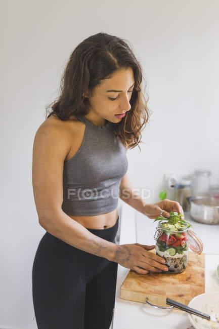 Жінка готує салат, щоб продовжувати рубати дошку. — стокове фото