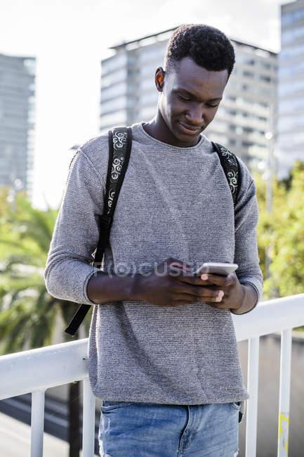 Jeune homme debout sur un pont, en utilisant un smartphone — Photo de stock
