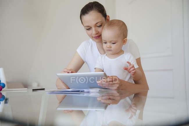 Madre e figlioletta utilizzando tablet insieme a casa — Foto stock