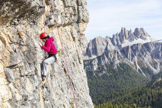 Italy, Cortina d 'Ampezzo, woman climbing in the Dolomites mountains — стоковое фото