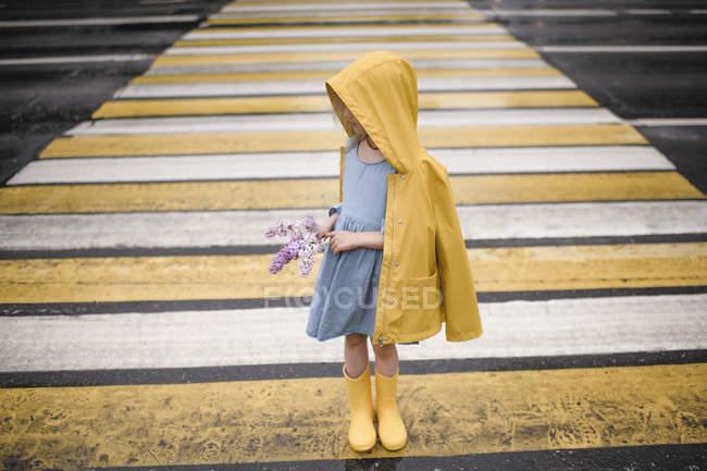 Ragazza che indossa racchetta gialla, in piedi sul passaggio zebra, tenendo lilla — Foto stock