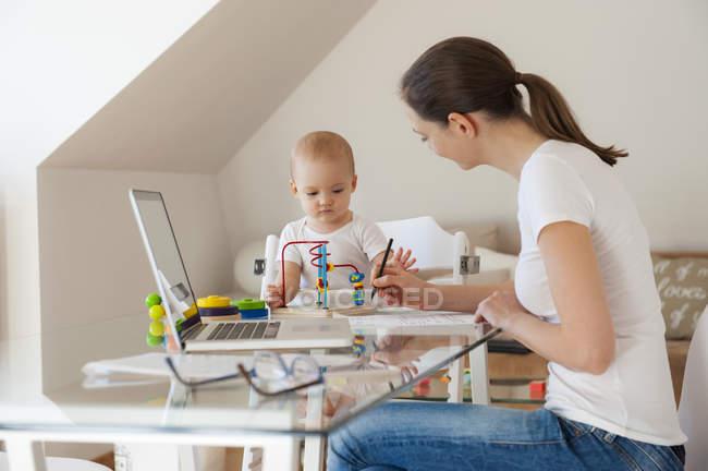 Мати користується ноутбуком, а дочка грає вдома за столом. — стокове фото