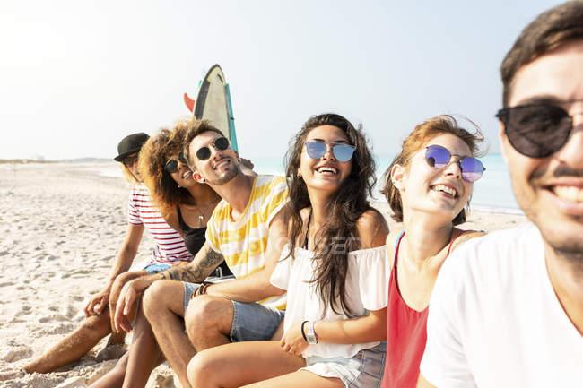 Amici seduti sulla spiaggia, divertirsi — Foto stock