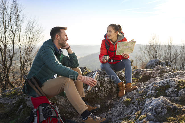 Happy couple on a hiking trip in the mountains having a break — Stock Photo