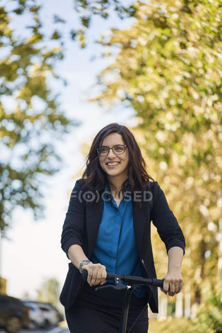 Portrait of smiling businesswoman with scooter — Stock Photo
