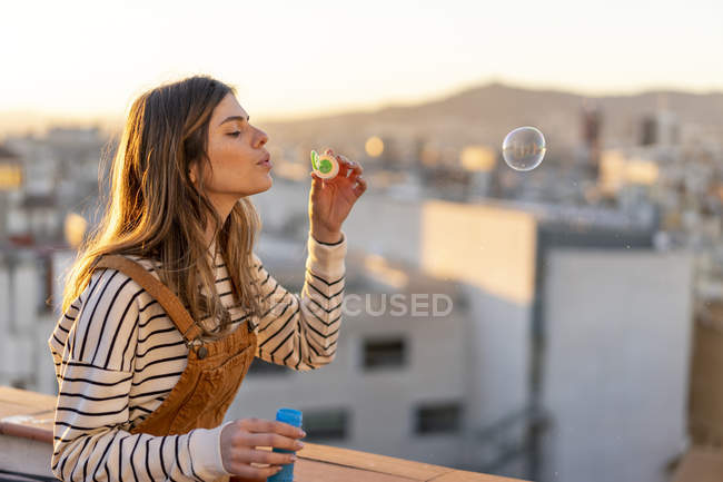 Young woman blowing soap bubbles on roof terrace in the evening — Stock Photo