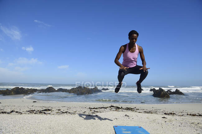 Sportive woman jumping on the beach — Stock Photo