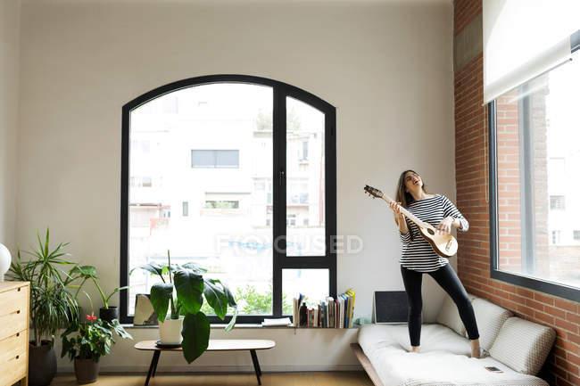 Felice giovane donna in piedi sul divano a casa e suonare la chitarra — Foto stock