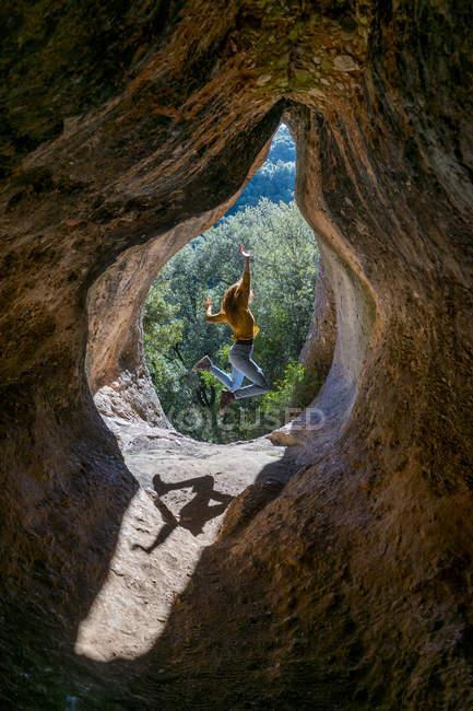 Молода жінка стрибає в печерному вході, Кова - Сіманья (Барселона, Іспанія). — стокове фото