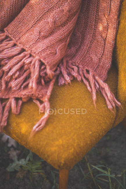 Blanket on orange chair outdoors — Stock Photo