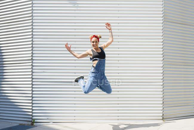 Souriant jeune femme sautant dans les airs — Photo de stock