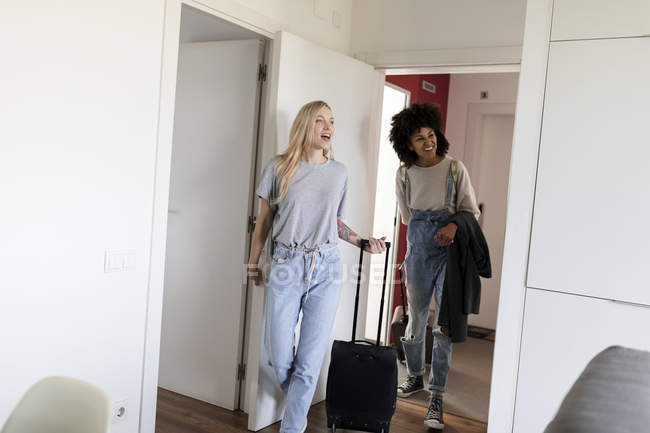 Two happy women with baggage arriving in accomodation — Stock Photo
