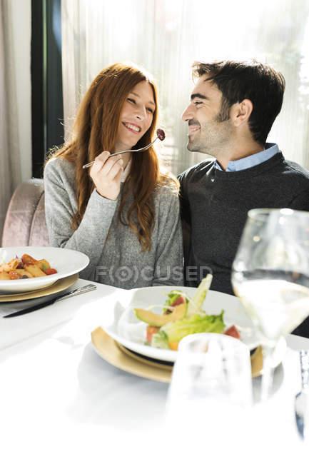 Усміхнена жінка дозволяючи людині спробувати їжу в ресторані — стокове фото