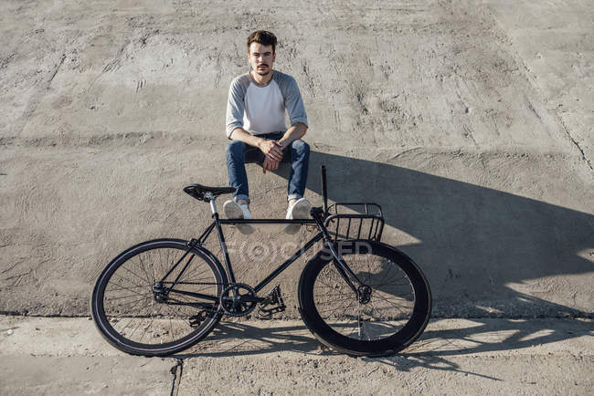 Young man with commuter fixie bike having a break and sitting on concrete wall — Stock Photo