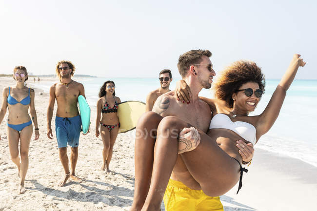Friends walking on the beach, one man carrying his girlfriend — Stock Photo