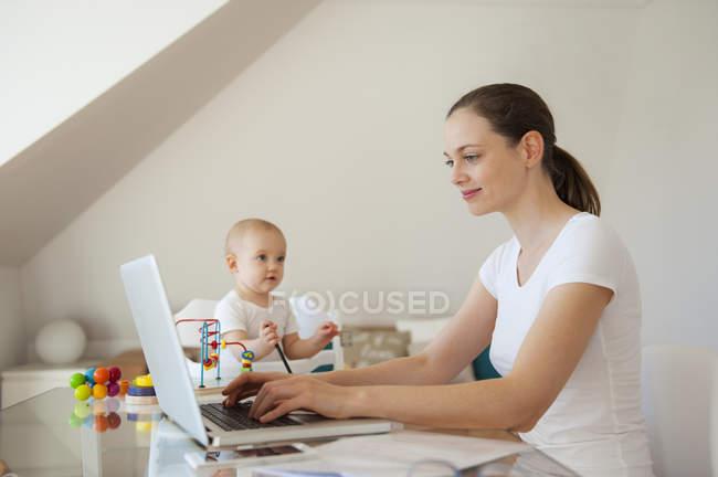 Sorridente madre utilizzando laptop e figlioletta che gioca a tavola a casa — Foto stock