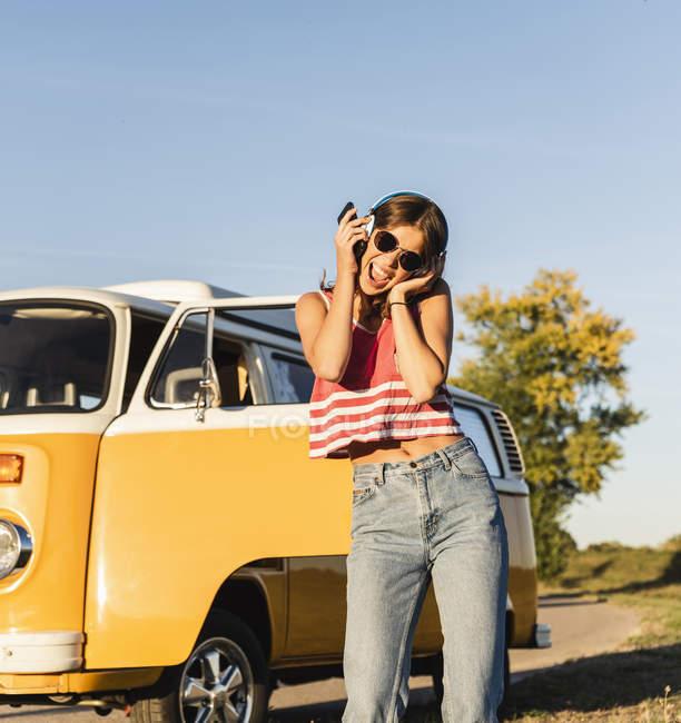 Красивая женщина в дороге со своим трейлером, танцует, слушает музыку — стоковое фото