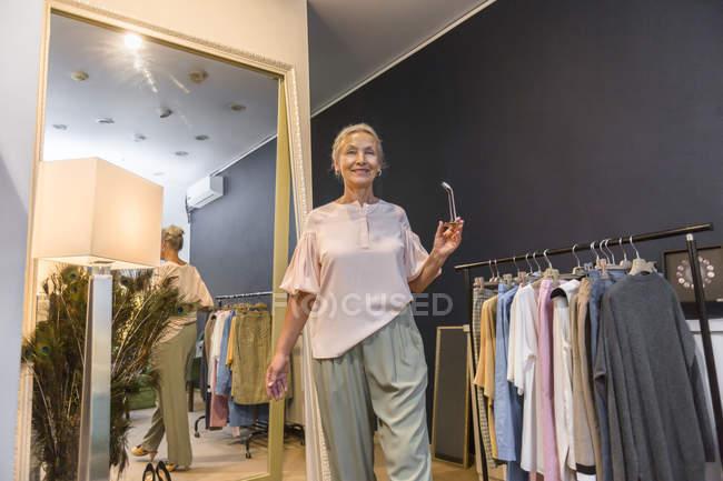 Улыбающаяся пожилая женщина, идущая в бутике, отраженная в зеркале — стоковое фото
