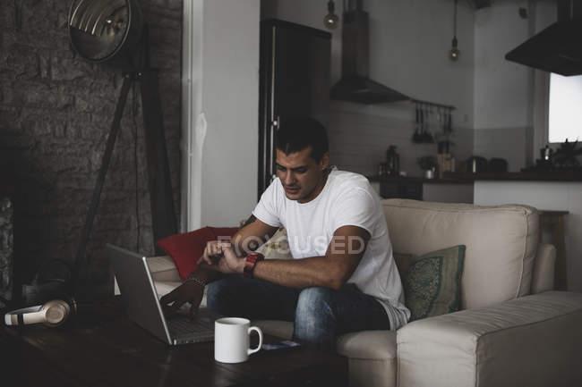 Giovane seduto sul divano a casa utilizzando il computer portatile e controllando l'ora — Foto stock