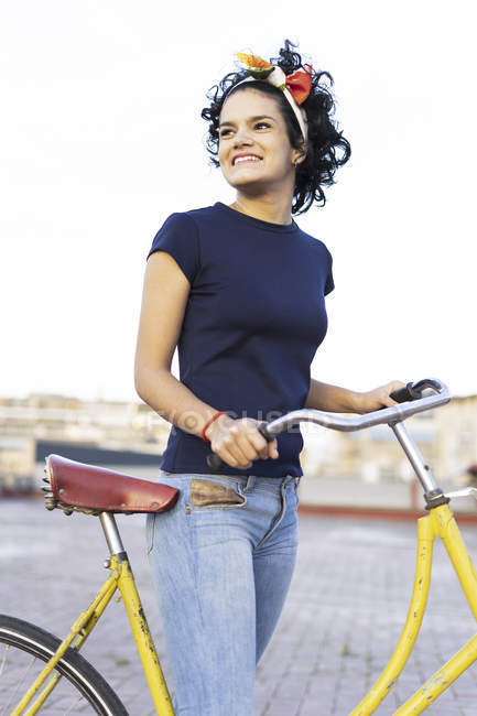 Happy young woman with bicycle in the city — Stock Photo