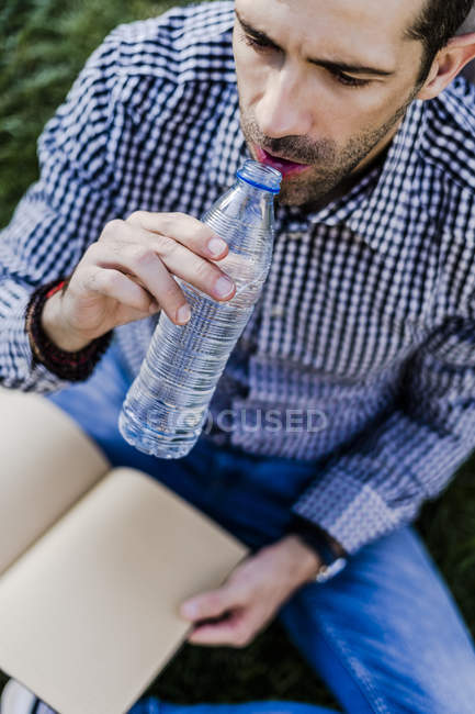 Man sitting on a meadow drinking water — Stock Photo