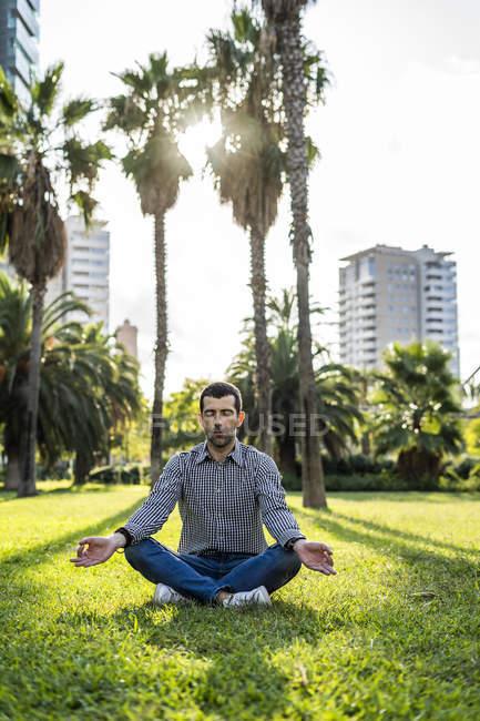 Мужчина, сидящий на лугу в городском парке и занимающийся йогой — стоковое фото