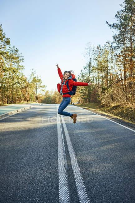 Mujer alegre saltando por un camino vacío durante el viaje de mochila. - foto de stock