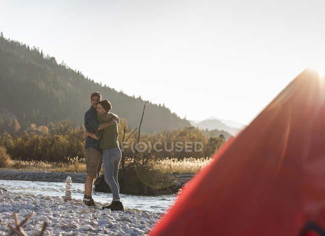 Pareja madura acampando en la orilla del río en la luz de la noche - foto de stock
