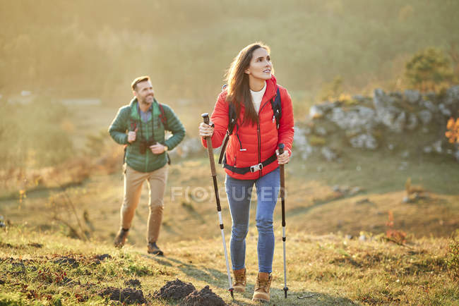 Couple walking on alpine meadow on a hiking trip in the mountains — Stock Photo