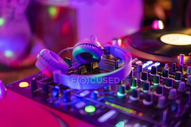 Headphones on illuminated mixing board — Stock Photo
