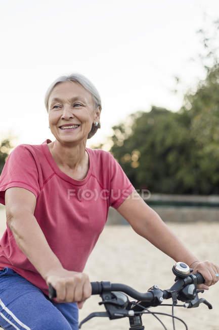 Ritratto di donna anziana sorridente in bicicletta — Foto stock