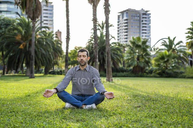 Man sitting on meadow in city park doing yoga exercise — Stock Photo