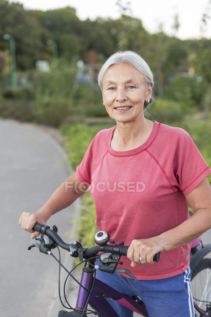 Portrait of senior woman with bicycle — Stock Photo
