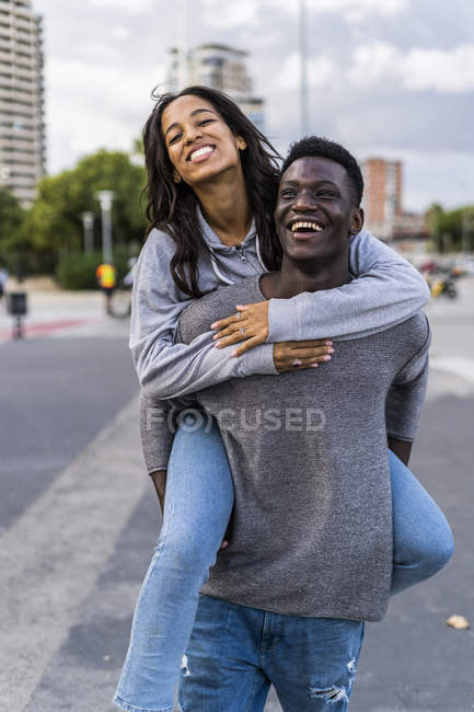 Young man carrying his girlfriend piggyback in the street — Stock Photo