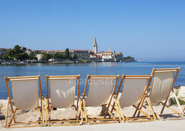 Croatia, Istria, Porec, Old town, Euphrasian Basilica, beach loungers in the foreground — стокове фото