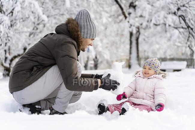 Счастливый отец играет с дочерью в зимнем пейзаже — стоковое фото