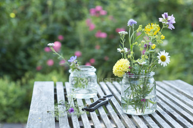 Wildflowers in preserving jars on garden table — Stock Photo