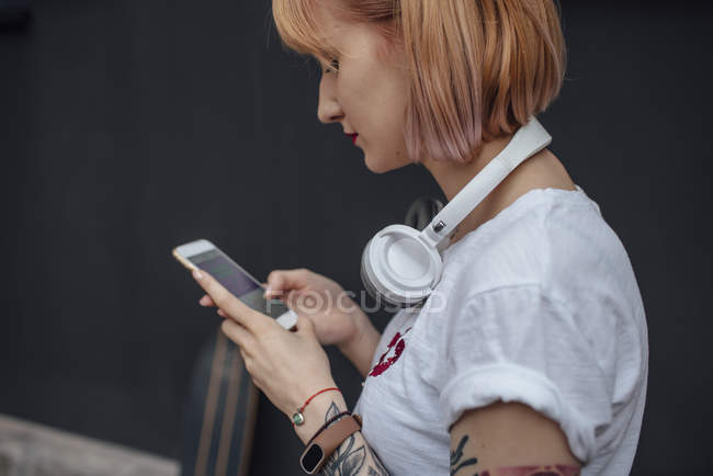 Young woman with headphones using cell phone — Stock Photo