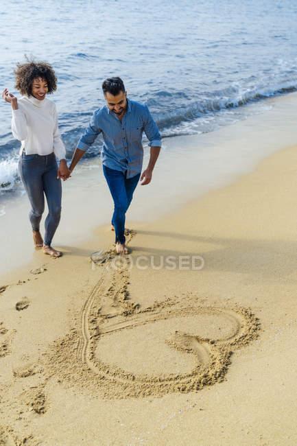 Spanien, Barcelona, glückliches Paar, das Spaß am Strand hat und ein Herz in den Sand zieht — Stockfoto