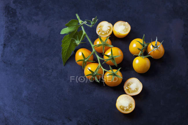 Whole and sliced cherry tomatoes 'Golden Nugget' on dark ground — Stock Photo